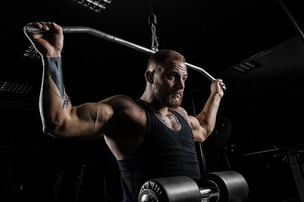 Professionele atleet voert een oefening uit in de sportschool. trekt de stang naar de achterkant van het hoofd. oefening voor de ontwikkeling van de rugspieren