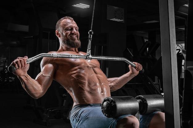 Professionele atleet voert een oefening uit in de sportschool. trekt de stang naar zijn borst. oefening voor het pompen van de rug.