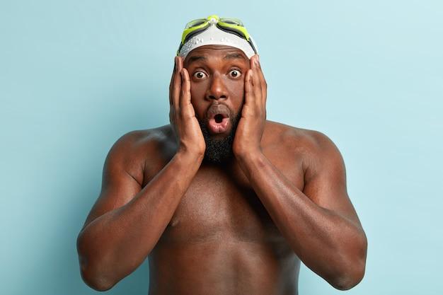 Professionele atleetzwemmer raakt wangen en kijkt met omg-uitdrukking, is een actieve sportman, heeft een donkere huid, draagt een zwemmuts en -bril, geschokt dat zijn team de concurrentie verliest.