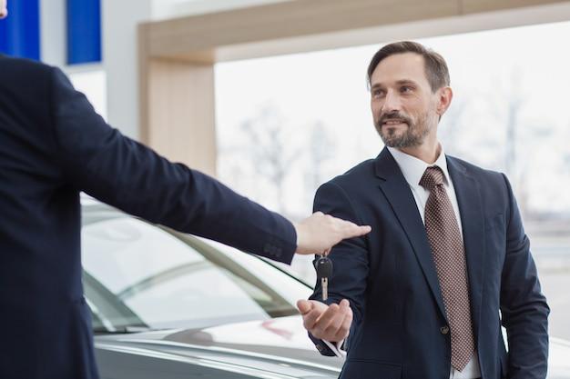 Professionele autodealer die sleutels doorgeeft aan zijn klant, eigenaar van een nieuwe auto