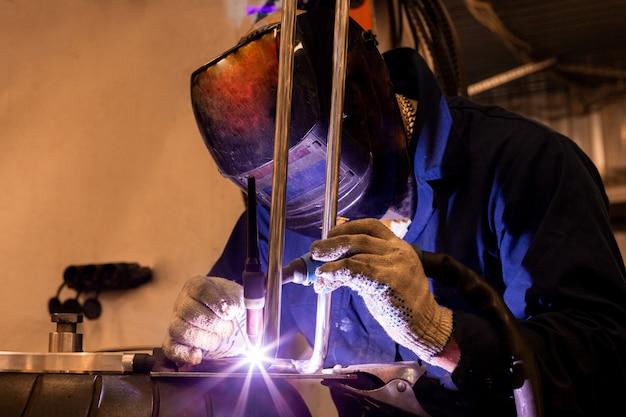 Professionele automonteur die in de autoreparatiedienst aan de snijmachine van het argongas werkt