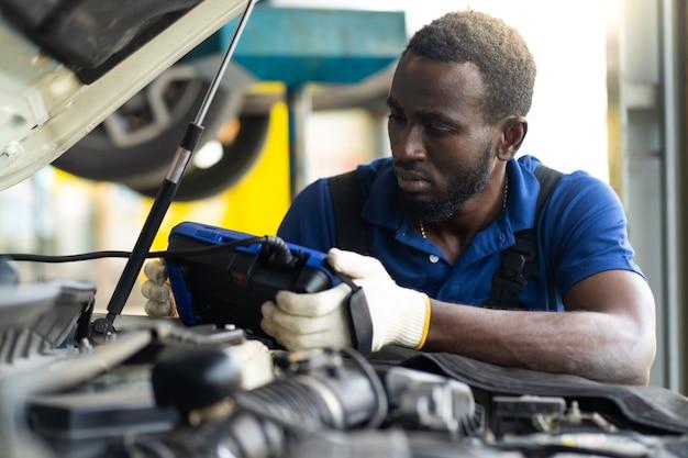 Professionele automonteur reparatieservice en controle van de automotor door diagnostics software-computer. expertise monteur werken in auto reparatie garage.