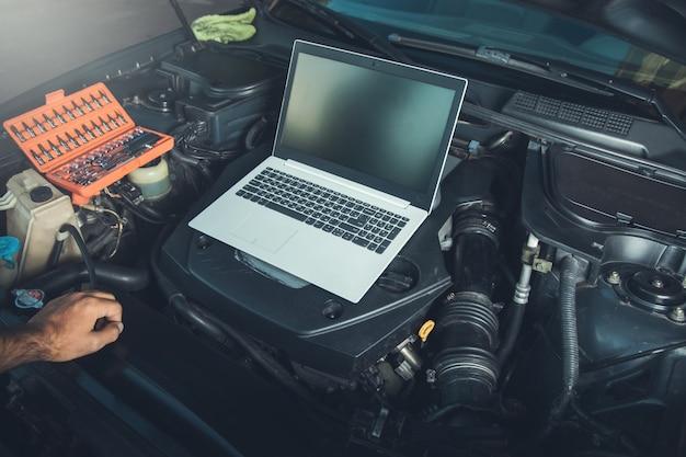 Professionele automonteur werken in auto reparatieservice met laptop op auto