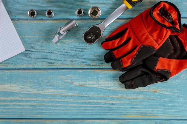 Professionele automotive tool set moersleutels verchroomd gereedschap met kladblok beschermende handschoenen op hout.