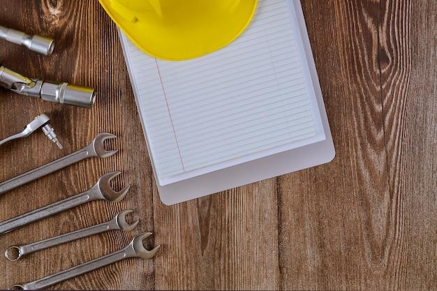 Professionele automotive tool set moersleutels verchroomd gereedschap met spiraal notitieblok op hout.
