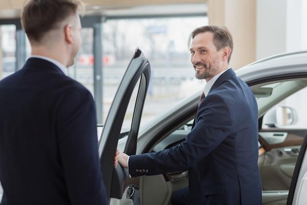 Professionele autoverkoper die zijn cliënt helpen die een nieuwe auto kiezen