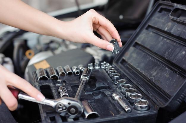 Professionele autovrouwwerktuigkundige en man reparatie auto in openlucht.