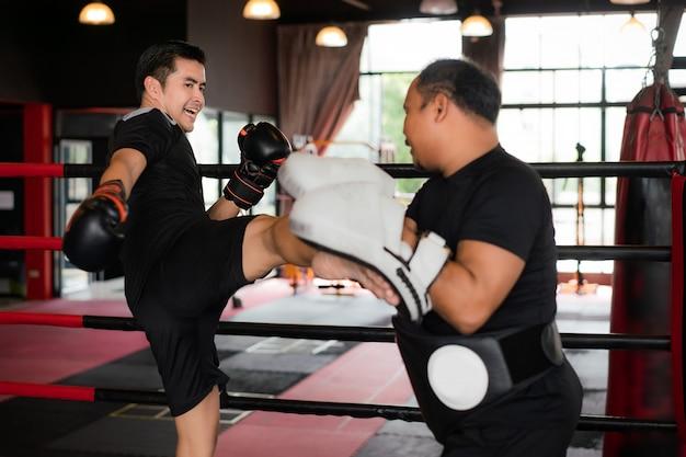 Professionele aziatische kickbokser die professionele trainer in boksstadion schopt