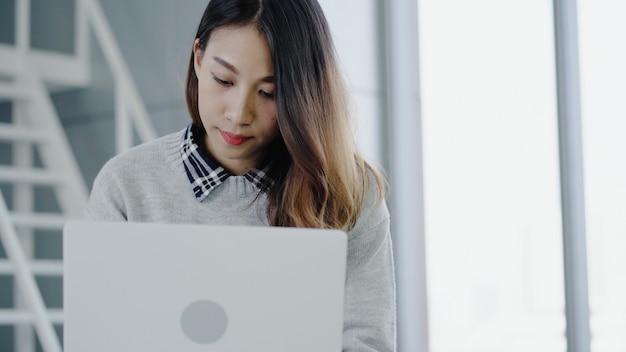 Professionele aziatische onderneemster die op haar kantoor via laptop werkt. jonge aziatische vrouwelijke manager die draagbaar computerapparaat met behulp van terwijl het zitten op moderne werkplaats.