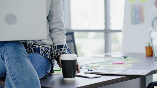 Professionele aziatische onderneemster die op haar kantoor via laptop werkt.
