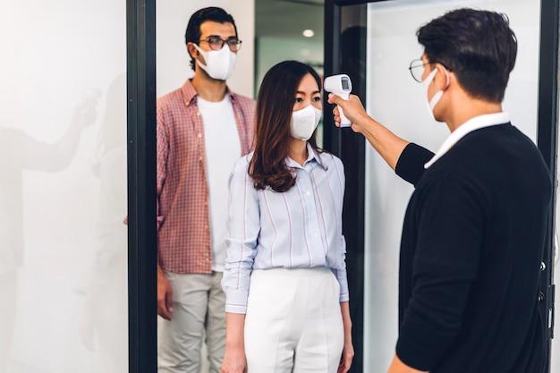 Professionele aziatische zaken die een infraroodthermometer gebruiken die de temperatuur controleert met een beschermend masker;