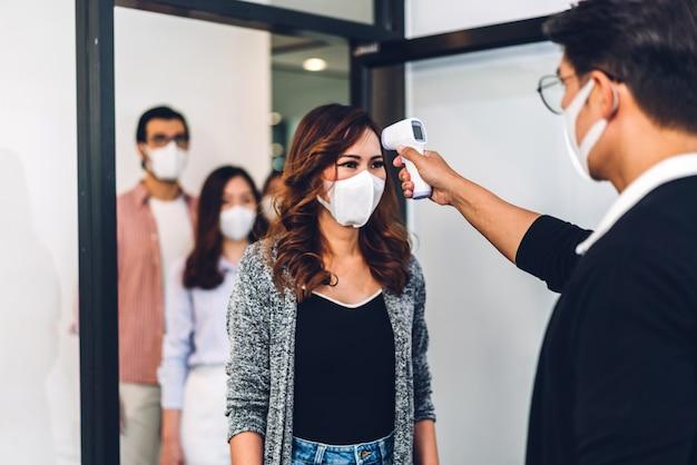 Professionele aziatische zaken en het gebruik van een infraroodthermometer die het lichaam controleert met een beschermend masker;