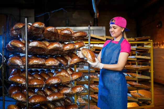 Professionele bakker - een jonge, mooie vrouw in een jeansschort houdt vers brood vast tegen de achtergrond van een bakkerij of bakkerij. bakkerijproducten. broodproductie