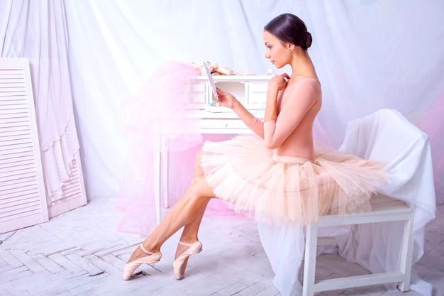 Professionele balletdanser die in de spiegel op roze kijkt