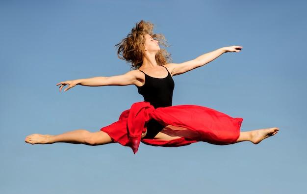 Professionele balletdanser springen met rode stof op zonsondergang zon.