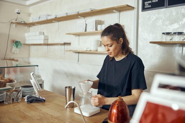 Professionele barista die koffie bereidt met behulp van chemex giet over koffiezetapparaat en lekketel.