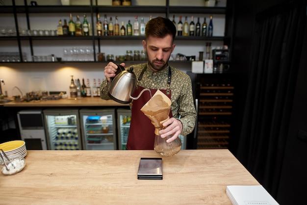 Professionele barista die koffie bereidt met chemex giet over koffiezetapparaat en lekbak. alternatieve manieren om koffie te zetten. koffie winkel concept.