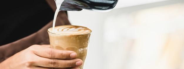 Professionele barista die latte art-koffie maakt