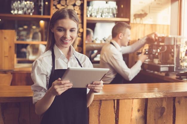 Professionele barista. jonge man in schort aan het werk bij toog met koffiezetapparaat. vrouw met behulp van tablet pc