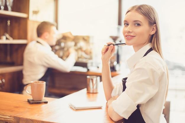 Professionele barista. jonge man in schort aan het werk bij toog met koffiezetapparaat. vrouw neemt de bestelling op en kijkt naar de camera