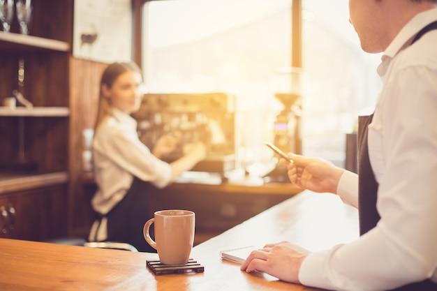Professionele barista. jonge vrouw in schort werken bij toog met koffiezetapparaat. man die de bestelling opneemt