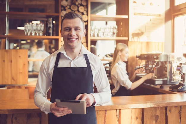 Professionele barista. jonge vrouw in schort werken bij toog met koffiezetapparaat. man met behulp van tablet pc