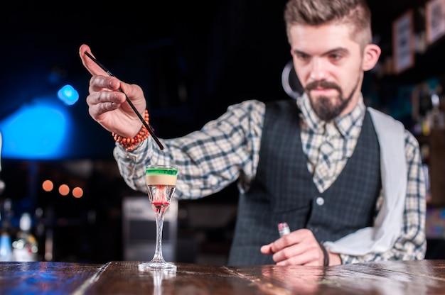 Professionele barman demonstreert zijn vaardigheden over de toonbank aan de bar
