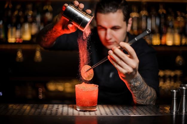 Professionele barman die aan een alcoholische cocktail in het glas een gedroogde sinaasappel toevoegt met een pincet en aromatisch poeder in het rode licht op de toog.