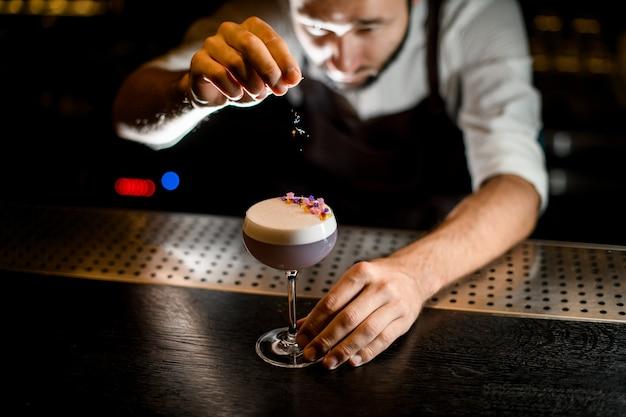 Professionele barman die besprenkelen op het uitschot van de lichtviolette cocktail met gele en paarse bloembloemblaadjes