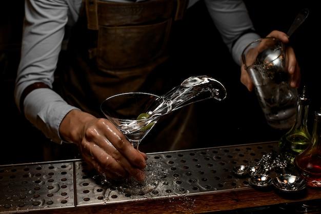 Professionele barman die een alcoholische drank in het martini-glas mengt met één olijf