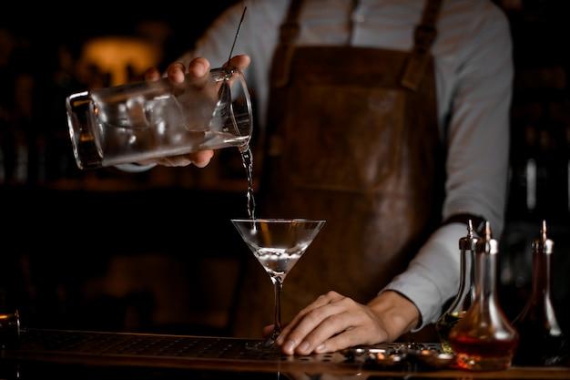 Professionele barman die een alcoholische drank van de maatbeker op het martini-glas giet