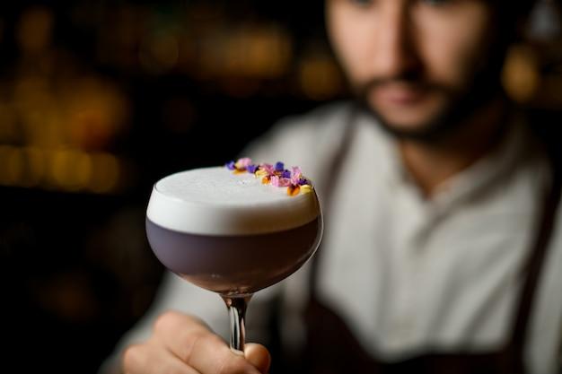 Professionele barman die een cocktail met wit schuim serveert versierd met bloemblaadjes in de bar