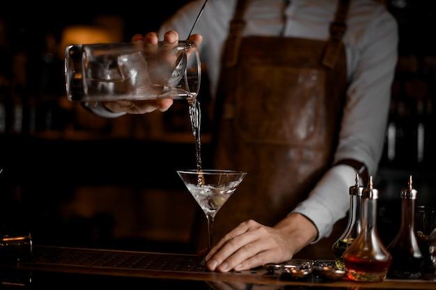 Professionele barman die een transparante alcoholische drank van de maatbeker op het martini-glas schenkt