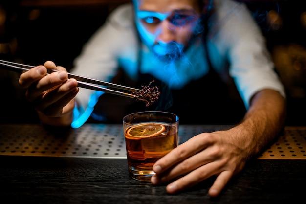 Professionele barman die gekoelde bruine karamel met twezzers toevoegt aan de cocktail met ijsblokjes onder blauw licht