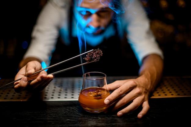 Professionele barman die gekoelde smeltende karamel met twezzers toevoegt aan de cocktail met ijsblokjes onder blauw licht
