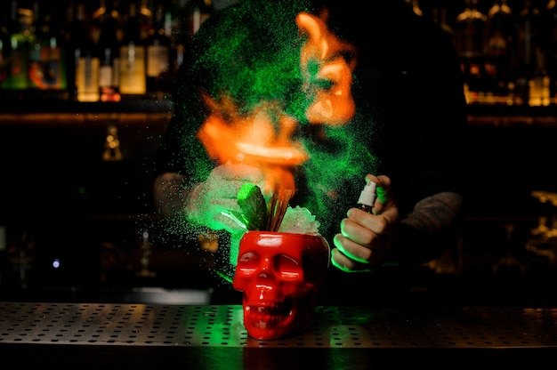 Professionele barman sproeit op de cocktail in de rode scull-beker van de verdamper en vlamt deze in het groene licht op de toog