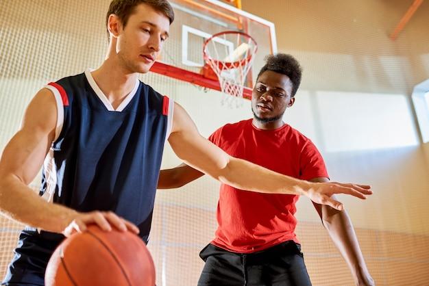 Professionele basketbalspeler die dichtbij de mand van de concurrent dribbelt