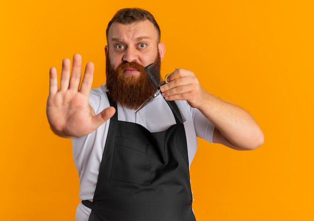 Professionele bebaarde kapper man in schort houden schaar en haarborstel stopbord met hand met angst expressie staande over oranje muur maken