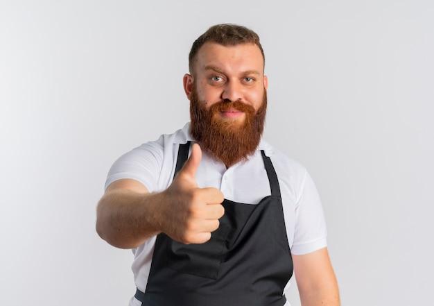 Professionele bebaarde kapper man in schort met blij gezicht lachend duimen opdagen staande over witte muur