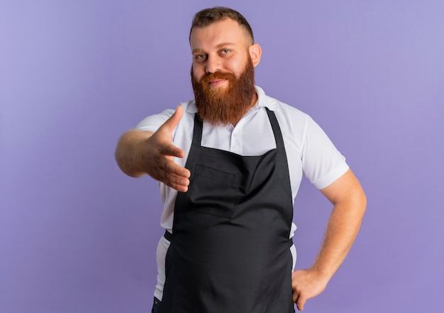 Professionele bebaarde kapper man in schort met zelfverzekerde uitdrukking biedt handgroet staande over paarse muur