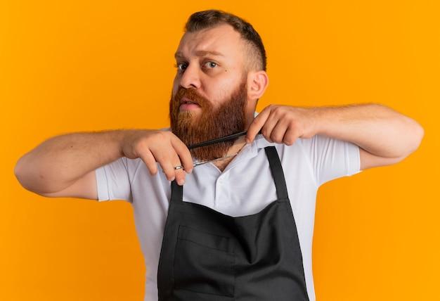 Professionele bebaarde kapper man in schort zijn baard kammen en knippen met een schaar op zoek zelfverzekerd staande over oranje muur