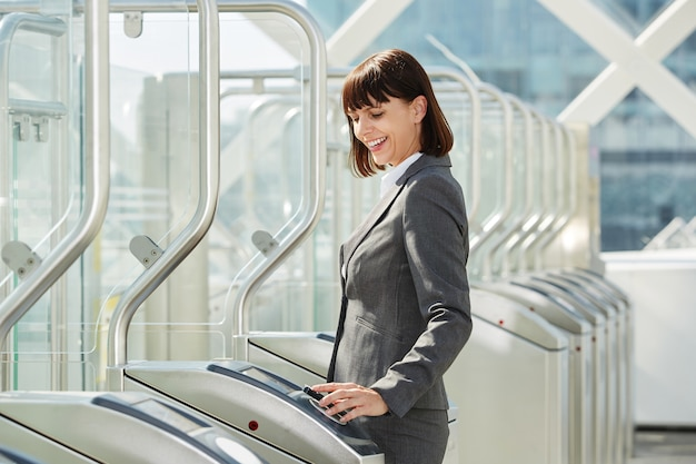 Professionele bedrijfsvrouw die door platformbarrière loopt