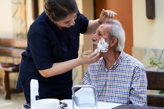 Professionele behulpzame verzorger en een senior man tijdens huisbezoek