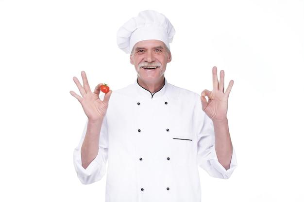 Professionele bejaarde chef-kok in wit uniform en hoed, met tomaat terwijl hij op de witte muur blijft