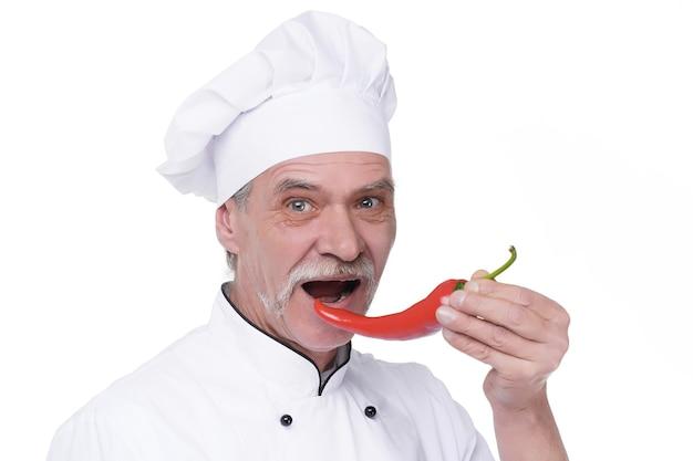 Professionele bejaarde chef-kok met rode peper op witte muur. blije chef-kok met groenten