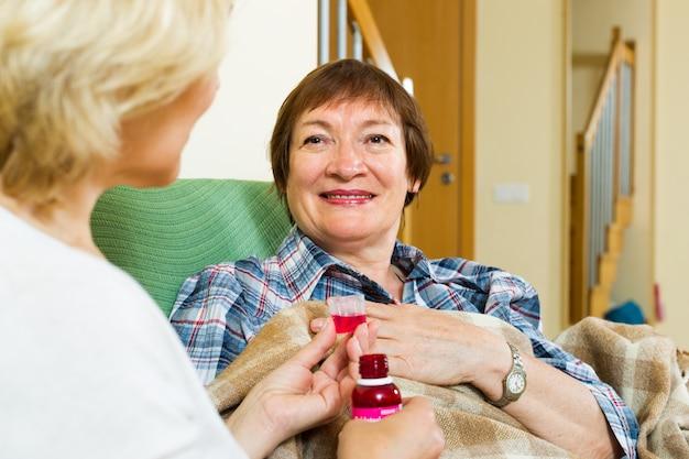 Professionele bejaardentehuismedewerker die mengsel aan patiënt aanbiedt