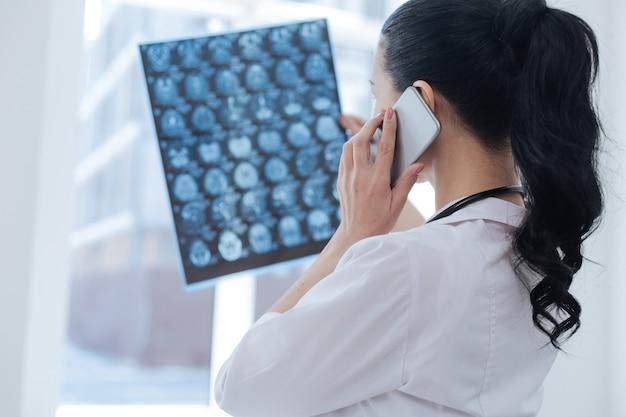 Professionele betrokken vrouwelijke oncoloog die bij de röntgenkabinet werkt tijdens het onderzoeken van de hersenscanafbeelding en het gebruik van een smartphone