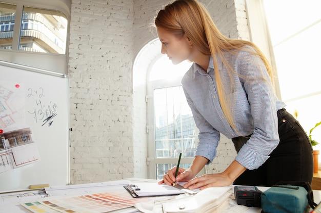 Professionele binnenhuisarchitect of architect die werken met kleurenpalet, kamertekeningen in modern kantoor.