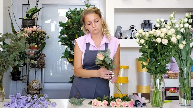 Professionele bloemist aan het werk in de bloemenwinkel. vrouw in uniform staat bij de tafel en maakt boeket