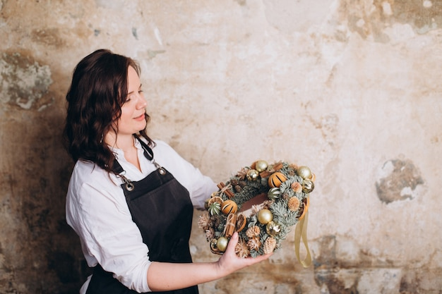 Professionele bloemist maakt boeket bloemen en nieuwjaar en kerstversiering
